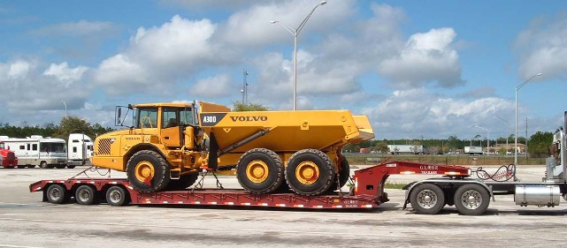 step deck trailer transporting earth moving equipment